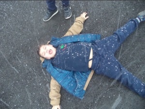 boy catching snowflakes